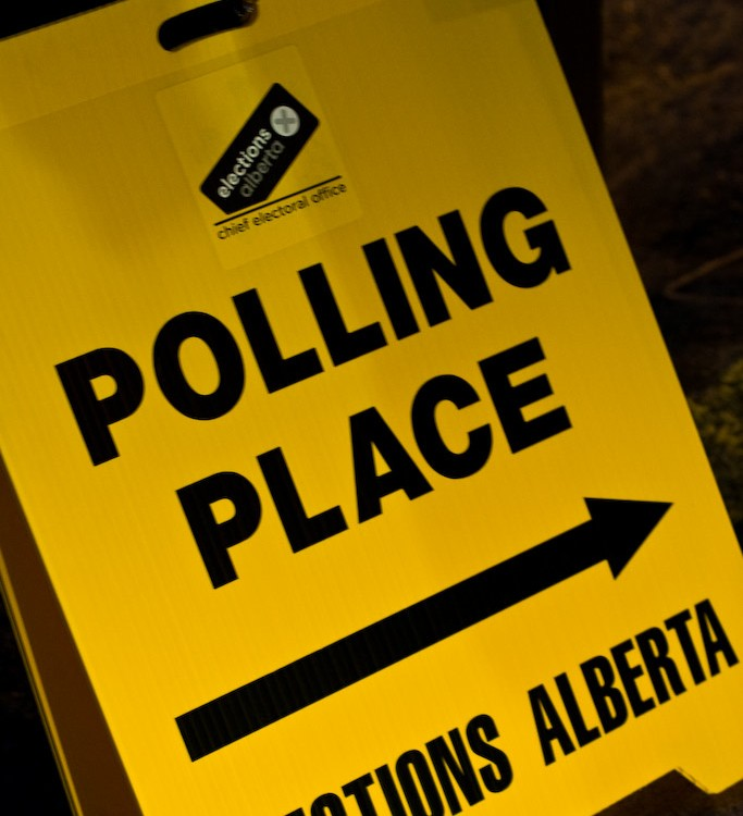 A yellow sign points to an Elections Alberta polling place