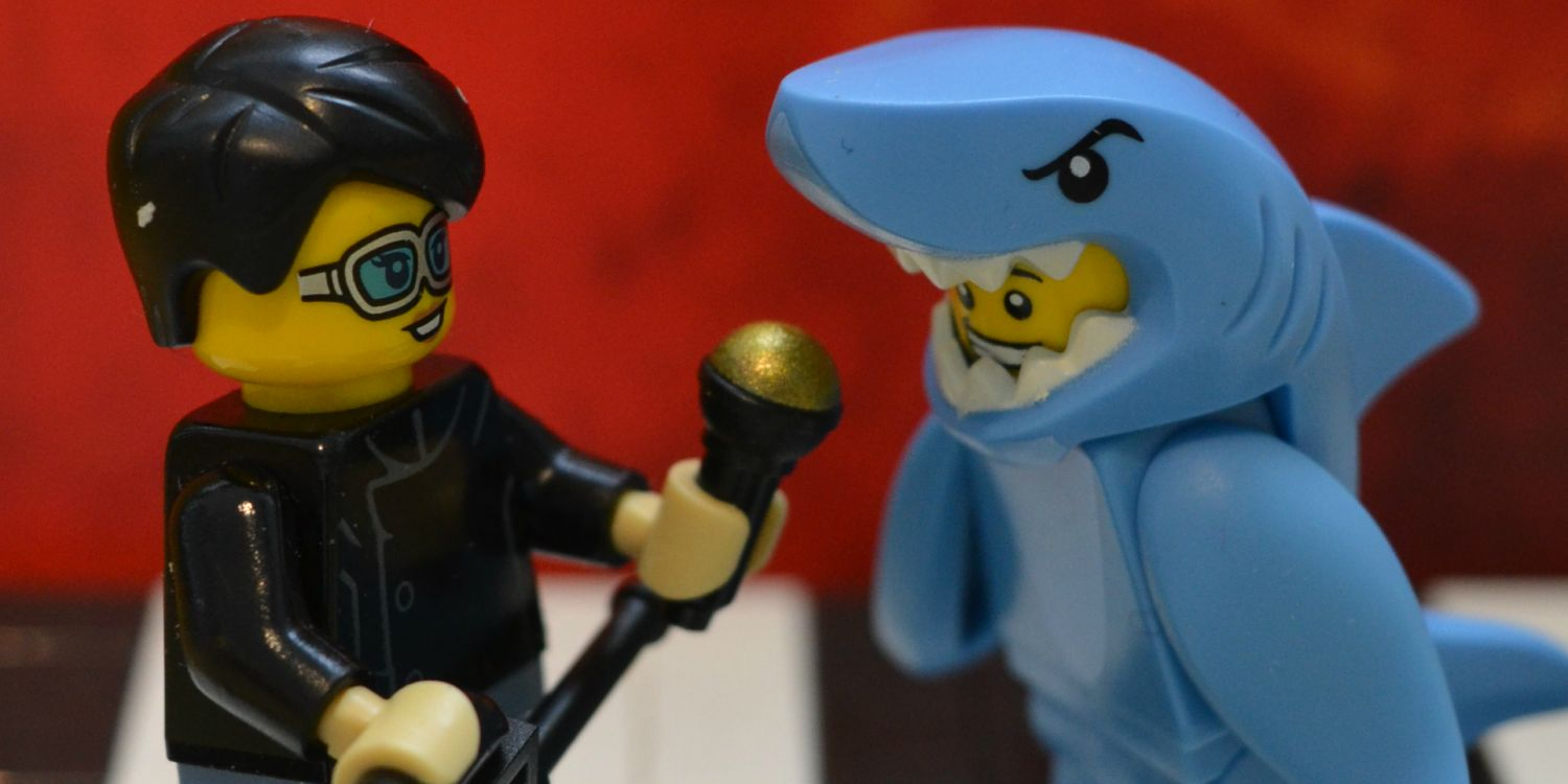 A Lego interviewer holds up a microphone to a Lego man dressed as a shark.