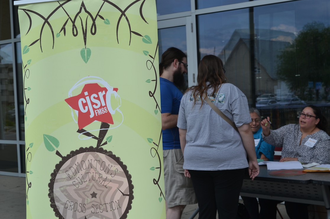 CJSR Banner in front of volunteers at a table