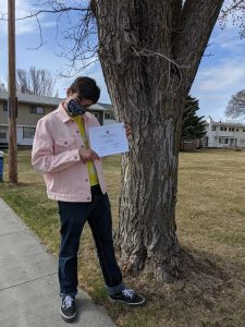 Kaden Peaslee holds up a graduation certificate in front of a tree